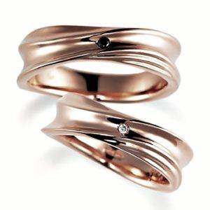 ピンクゴールドのペア結婚指輪、ウエーブデザイン。女性用はダイヤモンド入り、男性は黒ダイヤ、
