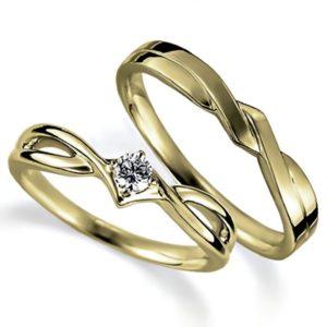 イエローゴールドのペア結婚指輪、抱き合わせアームデザイン、女性用は4本爪留めでダイヤモンド入り